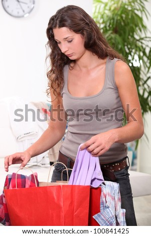 Woman searching through shopping bags - stock photo