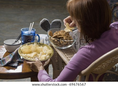 woman seated eating junk food - stock photo