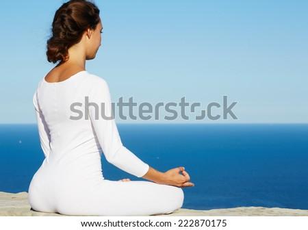 Woman seated in yoga pose on amazing sea background, woman meditating yoga enjoying sunny evening, brunette woman makes yoga meditation sitting on mountain hill on amazing altitude, meditating woman - stock photo