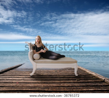 woman seated on a chaise-longue on a wharf - stock photo