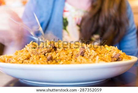 Woman seating in Chinese restaurant eating traditional: beef fried rice - stock photo