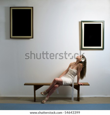 Woman seating on bench inside a gallery and looking at two picture frames.