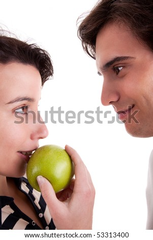 Woman seducing a man eating an apple, isolated on white background. Studio shot. - stock photo