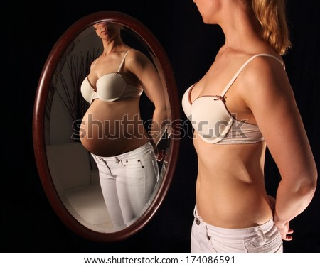 Woman seeing herself pregnant in a mirror - stock photo