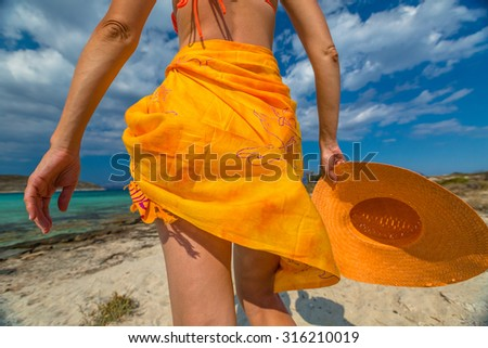 Woman seen from behind with orange sarong and wide brimmed hat on tropical beach. Elafonisos, the Greek version of the Maldives, the island's most exotic Mediterranean, Peloponnese, Greece.