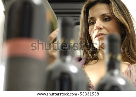Woman selecting a bottle of wine - stock photo