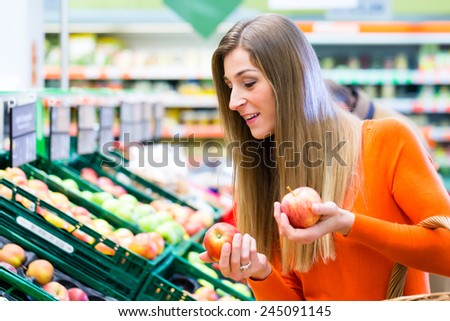 Woman selecting apples while grocery shopping in supermarket  - stock photo