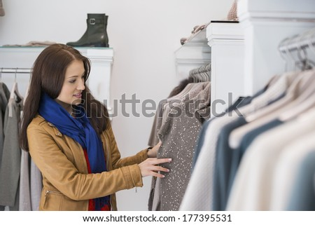 Woman selecting sweater in store - stock photo