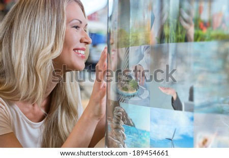 Woman selecting tv channel on glass touch screen - stock photo