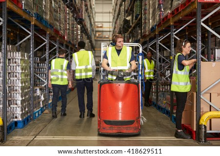 Woman selects box in warehouse for coworker on tow tractor - stock photo