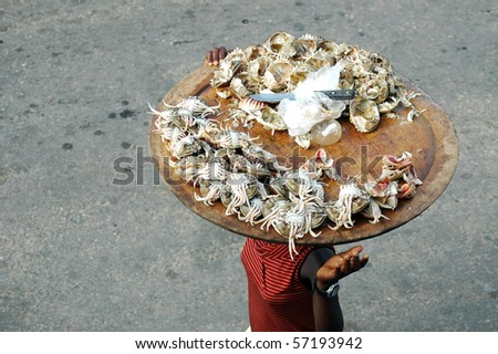 Woman selling crab meat on the street in africa - stock photo
