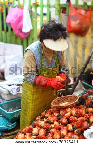 Woman selling sea pineapple and seafood in traditional Korean Wet Market - stock photo