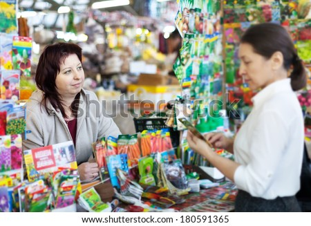 woman selling seeds to mature buyer in store for gardeners. Focus on seller - stock photo