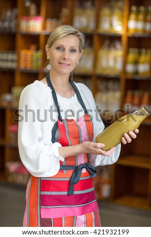 woman selling soup in grocery store - stock photo