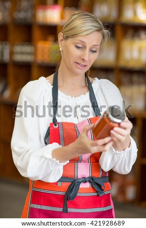 woman selling tomato sauce in grocery store - stock photo