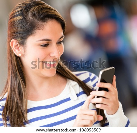 Woman sending a text from her mobile phone - stock photo