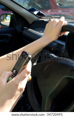 Woman sending a text message while driving a car - stock photo