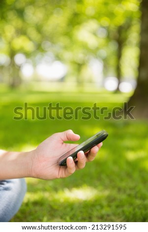 Woman sending a text on smartphone in the park on a sunny day