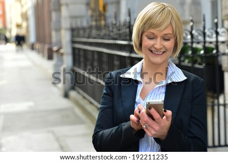 Woman sending text messages via mobile phone - stock photo