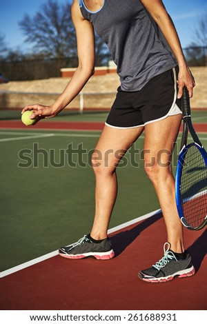 woman serving a tennis ball - stock photo