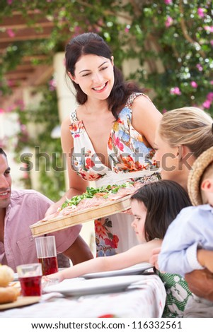 Woman Serving At Family Meal - stock photo