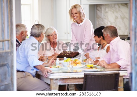 Woman Serving Cake To Group Of Friends Enjoying Meal At Home - stock photo