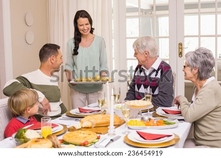Woman Serving Christmas Dinner To Her Family At Home In The Living Room