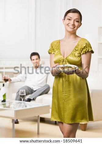 Woman serving elegant dinner to husband in livingroom - stock photo