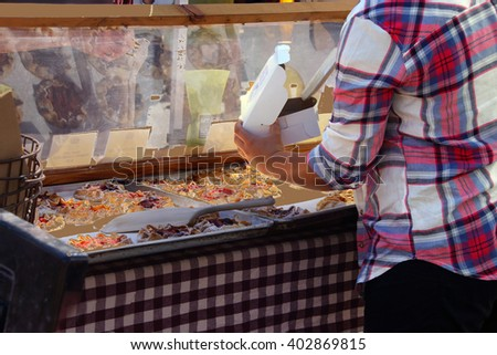 Woman serving pastries at the  Saturday Market,  Penticton, British Columbia, Canada