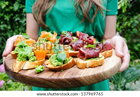 Woman serving platter of small mini bite size canapes, variety of bruschetta - stock photo