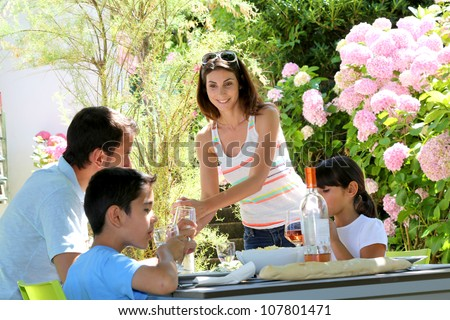 Woman serving water to family having lunch
