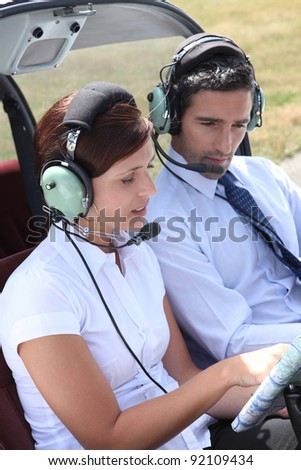 Woman setting a flight plan in an open cockpit - stock photo