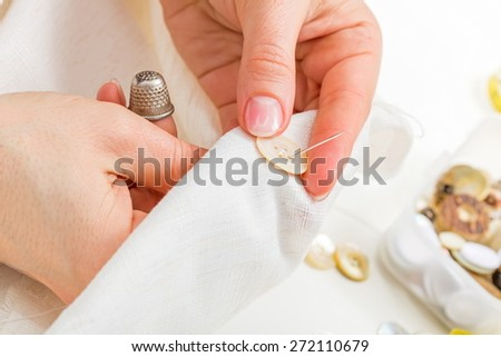 Woman sewing a button on cloth - stock photo