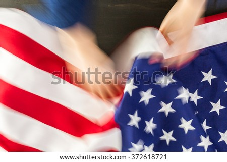 Woman sewing a large American Flag.