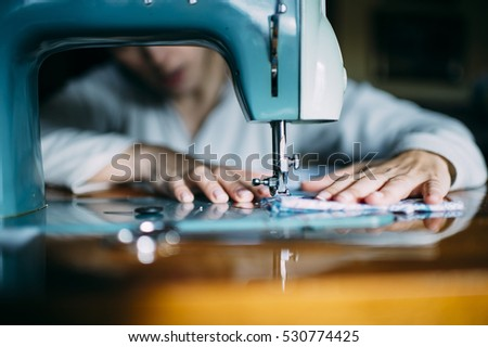 Woman sewing with a sewing machine in his workshop