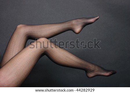Woman sexy legs in tights on black background - stock photo