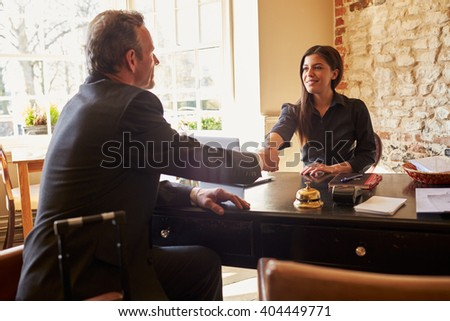 Woman shaking hands with guest at check-in desk of a hotel - stock photo