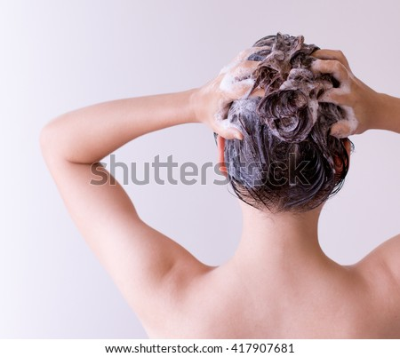 Woman shampooing her hair with both hands on her head in front of a white background. - stock photo
