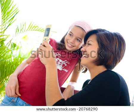 Woman sharing information on her cell phone with a younger child.