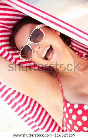 Woman Sheltering From Sun On Beach Holiday - stock photo
