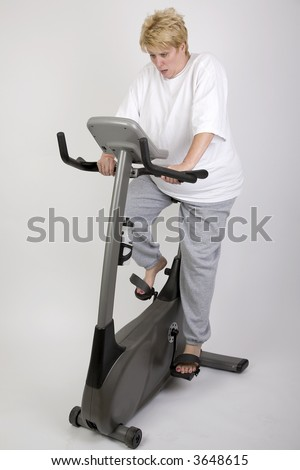 woman shocked at results on exercise bike - stock photo