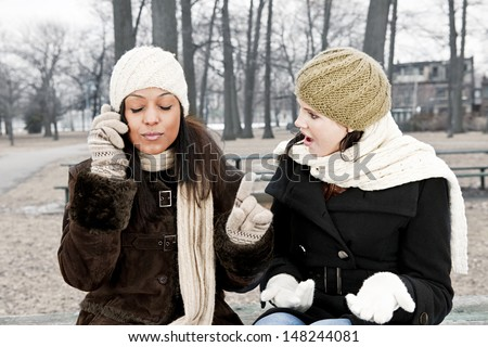 Woman shocked by friend ignoring her with phone call - stock photo