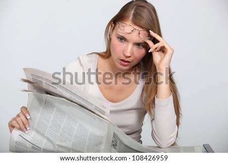 Woman shocked by newspaper article - stock photo