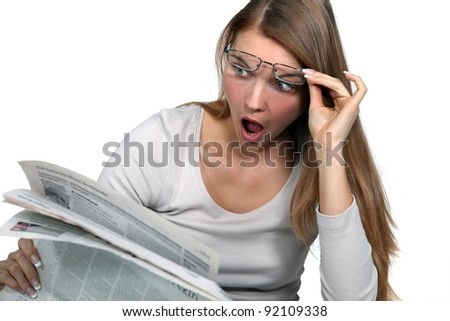 Woman shocked reading newspaper - stock photo