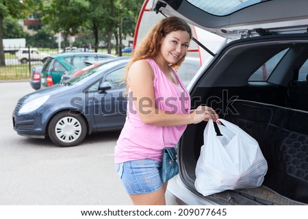 Woman shopper loading bag in trunk of her car on parking - stock photo