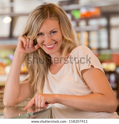 Woman shopping at the supermarket, standing near glass showcase and smiling at camera - stock photo