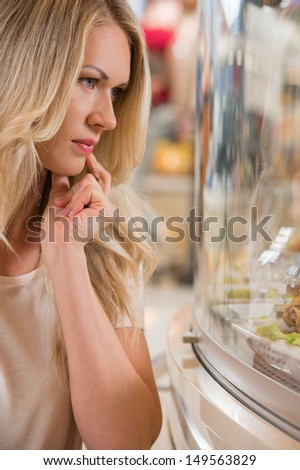 Woman shopping at the supermarket, standing near glass showcase and thinking what to choose - stock photo