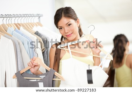 Woman shopping buying new dress in clothing shop choosing between two dresses. Beautiful multiracial caucasian / chinese asian female model looking in mirror smiling happy in clothing store. - stock photo
