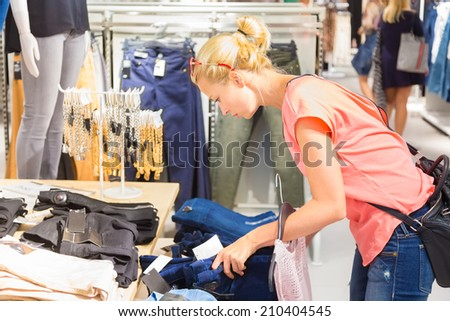 Woman shopping clothes. Shopper looking at clothing indoors in store. Beautiful blonde caucasian female model.  - stock photo
