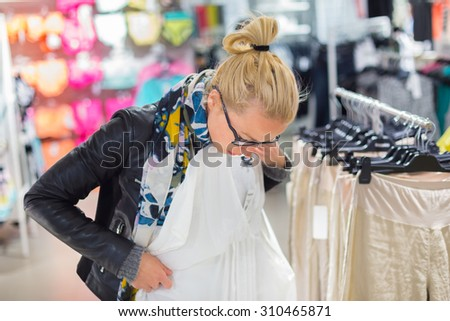 Woman shopping clothes. Shopper looking at clothing indoors in store. Beautiful blonde caucasian female model wearing black glasses, casual black leather jacket an colorful scarf. - stock photo